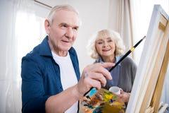 Hogere vrouw die echtgenoot het schilderen beeld bekijken royalty-vrije stock foto