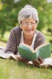 Hogere vrouw die een boek lezen bij park Royalty-vrije Stock Foto's