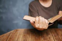 Hogere vrouw die een boek lezen bij woonkamer met oude wijnoogst tabl stock foto's