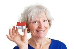 Hogere vrouw die een huis verkoopt Royalty-vrije Stock Foto