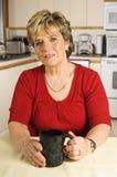Hogere vrouw die een koffiepauze in haar keuken neemt Stock Afbeeldingen