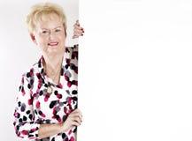 Hogere vrouw die een leeg wit teken houdt Stock Afbeeldingen