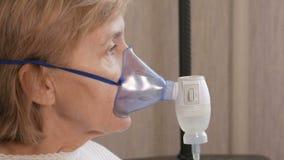 Hogere vrouw die een masker van een inhaleertoestel thuis houden Behandelt ontsteking van de luchtroutes via verstuiver Het verhi stock video