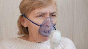 Hogere vrouw die een masker van een inhaleertoestel thuis houden Behandelt ontsteking van de luchtroutes via verstuiver Het verhi stock videobeelden