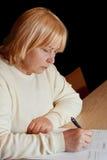Hogere vrouw die een officieel document invult Stock Foto