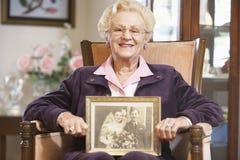 Hogere vrouw die een oude huwelijksfoto houdt stock fotografie
