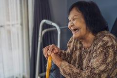 Hogere vrouw die en houten riet in woonkamer houden lachen stock afbeeldingen