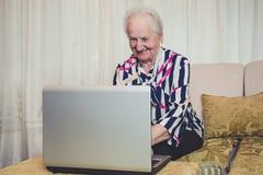 Hogere vrouw die en laptop glimlachen met behulp van stock foto