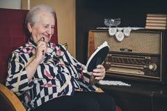 Hogere vrouw die en oud fotokader glimlachen bekijken royalty-vrije stock foto's