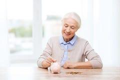 Hogere vrouw die geld thuis zetten aan spaarvarken Stock Foto's