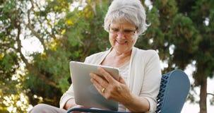 Hogere vrouw die gelukkig het Web op tablet surfen Royalty-vrije Stock Afbeelding