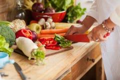 Hogere vrouw die groenten voorbereiden Stock Afbeeldingen