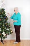 Hogere vrouw die haar Kerstmisboom verfraait Royalty-vrije Stock Foto