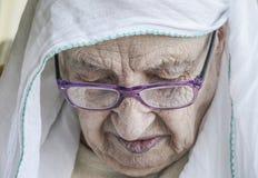 Hogere vrouw die headscarf terwijl het bidden dragen Stock Fotografie