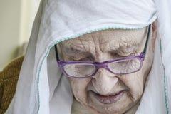 Hogere vrouw die headscarf terwijl het bidden dragen Stock Foto's