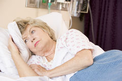 Hogere Vrouw die in het Bed van het Ziekenhuis ligt Stock Afbeeldingen