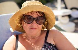 Hogere vrouw die hoed en zonnebril dragen bij strand Stock Foto's