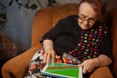 Hogere vrouw die Internet op een tablet surfen Royalty-vrije Stock Afbeeldingen