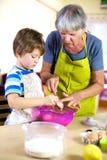 Hogere vrouw die kleinzoon helpt te koken en te bakken Stock Afbeeldingen