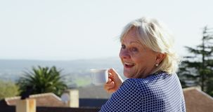 Hogere vrouw die koffie in balkon 4k hebben stock footage
