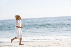 Hogere Vrouw die langs Sandy Beach lopen stock foto's
