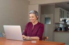Hogere vrouw die laptop met behulp van stock afbeeldingen