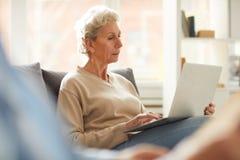 Hogere vrouw die laptop met behulp van stock fotografie