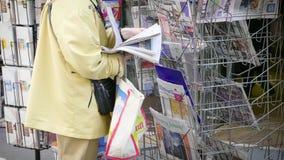 Hogere vrouw die lezingskranten selecteren bij kiosk stock videobeelden