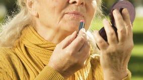 Hogere vrouw die lippenstift, schoonheidsverzorging voor bejaarden, anti-veroudert schoonheidsmiddelen toepassen stock video