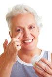 Hogere vrouw die lotion toepast stock afbeelding