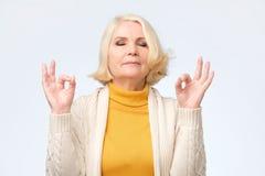 Hogere vrouw die meditatiegebaar met vingers doen stock fotografie
