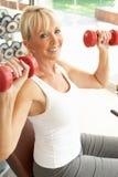 Hogere Vrouw die met Gewichten werkt Stock Foto's
