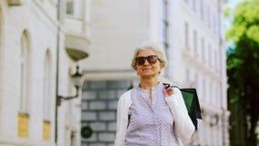Hogere vrouw die met het winkelen zakken in stad lopen stock videobeelden