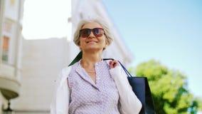Hogere vrouw die met het winkelen zakken in stad lopen stock video