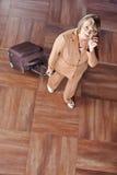 Hogere vrouw die met koffer telefoongesprek maken stock fotografie