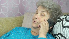 Hogere vrouw die met smartphone bij ruimte roept stock videobeelden