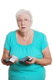 Hogere vrouw die met veel TV wordt verward remotes Stock Afbeelding