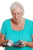 Hogere vrouw die met zo vele afstandsbedieningen wordt verward Stock Foto