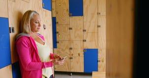 Hogere vrouw die mobiele telefoon in kleedkamer 4k met behulp van stock video