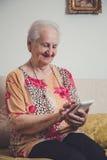 Hogere vrouw die mobiele telefoon met behulp van royalty-vrije stock afbeeldingen