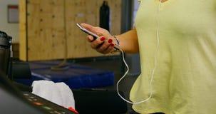 Hogere vrouw die mobiele telefoon met behulp van tijdens oefening in geschiktheidsstudio 4k stock videobeelden