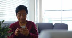 Hogere vrouw die mobiele telefoon in woonkamer met behulp van stock footage