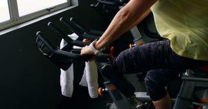Hogere vrouw die oefening op hometrainer 4k doen stock video