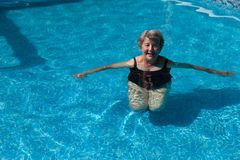 Hogere vrouw die oefeningen in een pool doen stock foto's