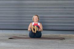 Hogere vrouw die oefeningen op een gymnastiekmat doen stock foto's