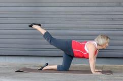 Hogere vrouw die oefeningen op een gymnastiekmat doen royalty-vrije stock foto's