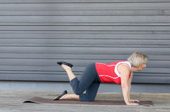 Hogere vrouw die oefeningen op een gymnastiekmat doen stock fotografie