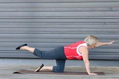 Hogere vrouw die oefeningen op een gymnastiekmat doen royalty-vrije stock afbeeldingen