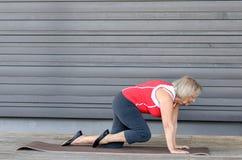 Hogere vrouw die oefeningen op een gymnastiekmat doen stock afbeeldingen