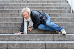 Hogere vrouw die onderaan steenstappen in openlucht vallen Royalty-vrije Stock Foto